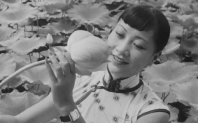 Anna May Wong looking at a lotus flower in