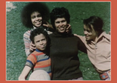 Three women and a boy smiling for the camera.