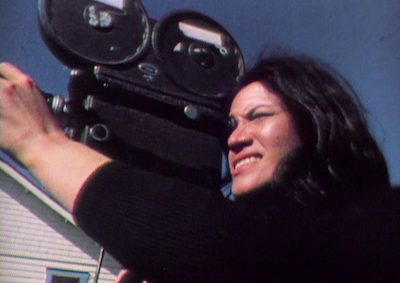 A person looking through a film camera.