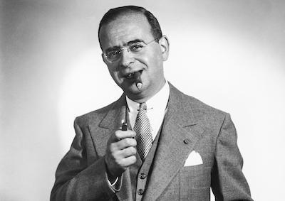 Max Steiner in a suit smoking a cigar.
