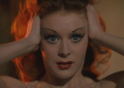 Moira Shearer with her hands on her head.