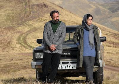 A man and a woman leaning against a car in an empty, hilly landscape.