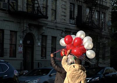 Two people holding red and white balloons in the street.